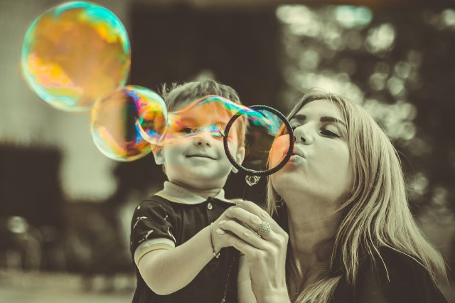 Mom blowing bubbles with kid