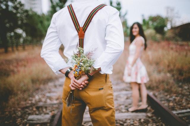 man holding flowers for girl