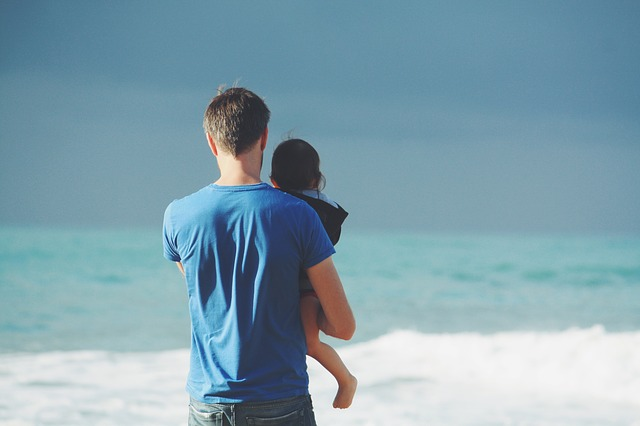 dad walking with his son on a beach