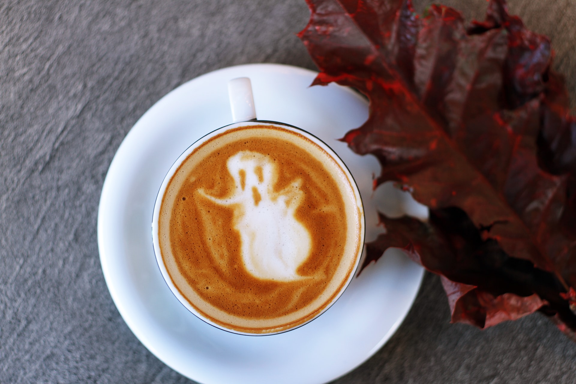 Cup of coffee with a ghost drawn in it