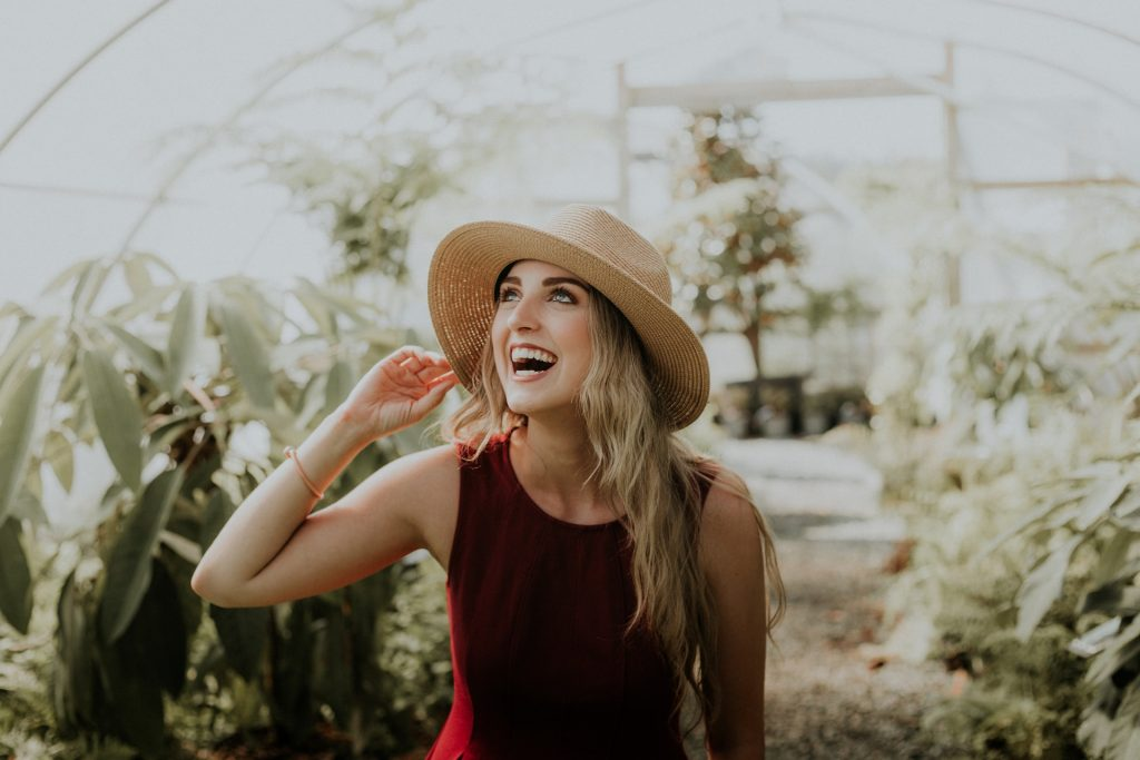 Smiling single woman in a red dress and a sun hat