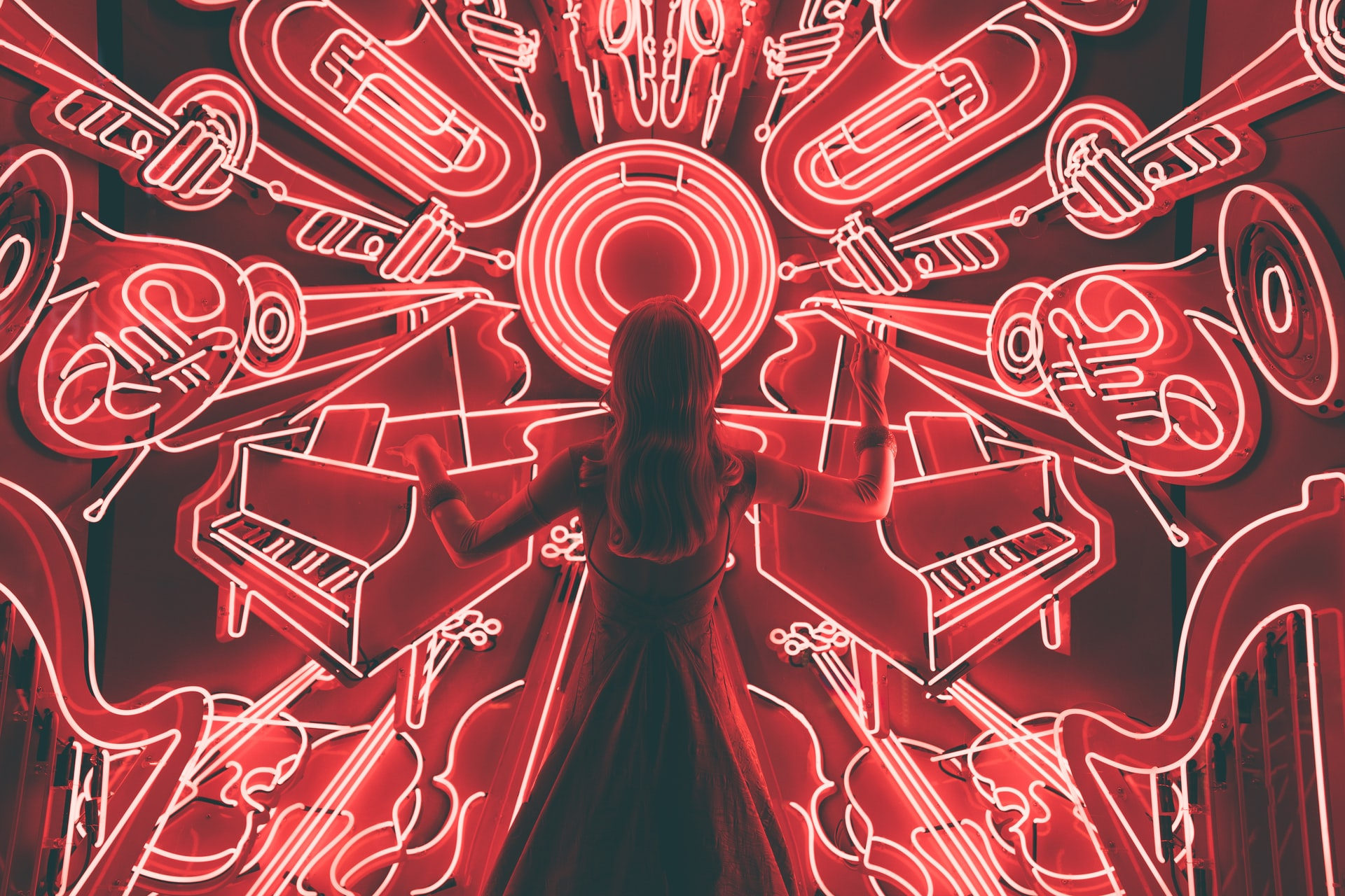 Girl composing music in front of an array of neon instruments