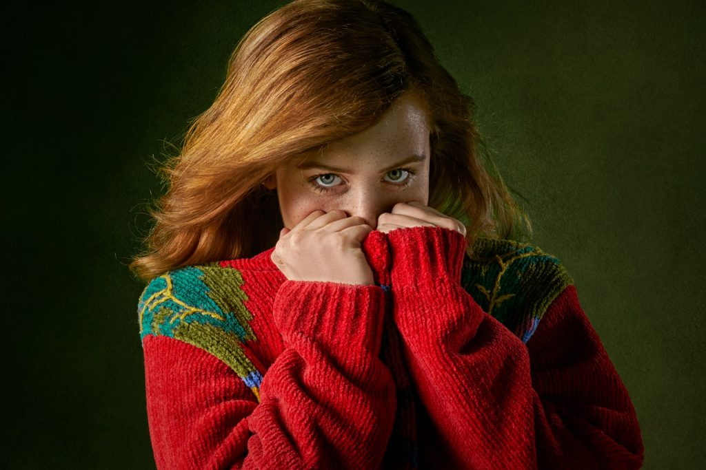 Shy woman in sweater covering her face